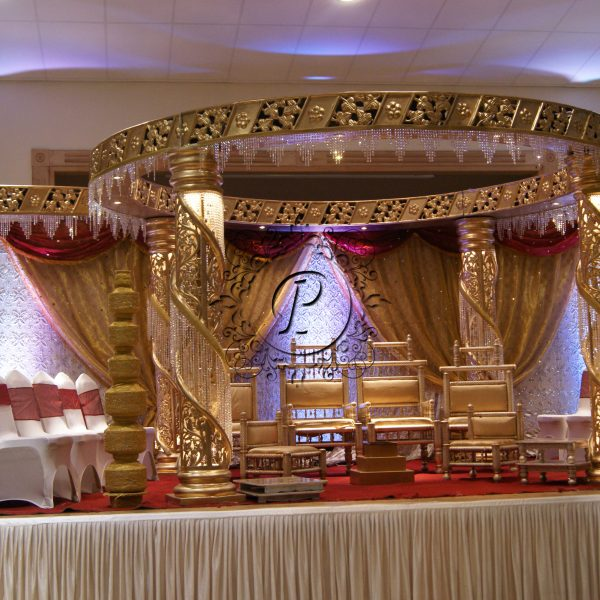 Gold Zali Mandap on stage with side seating